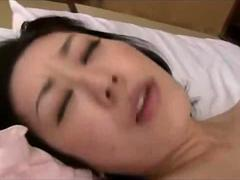 Japanese MILF in stockings gives a footjob to young guy