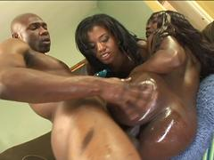 Large ass ebony bimbos oil up their behinds and indulge in a tempting threesome