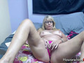 This granny is teasing naked on a webcam and masturbating with a dildo